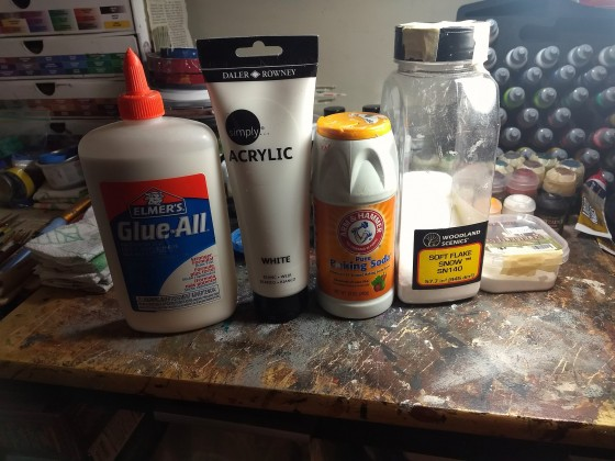 The secret ingredients for making snow paste effects:  PVA glue, white artists' acrylic paint, baking soda, and snow flock